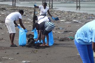 teens picking garbage in the seashore
